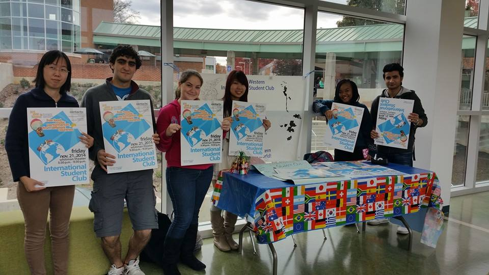 An International Student Club table with students, spreading the word about an upcoming event.