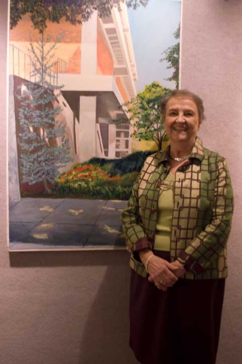 Artist Wright in front of panting of Anderson Hall
