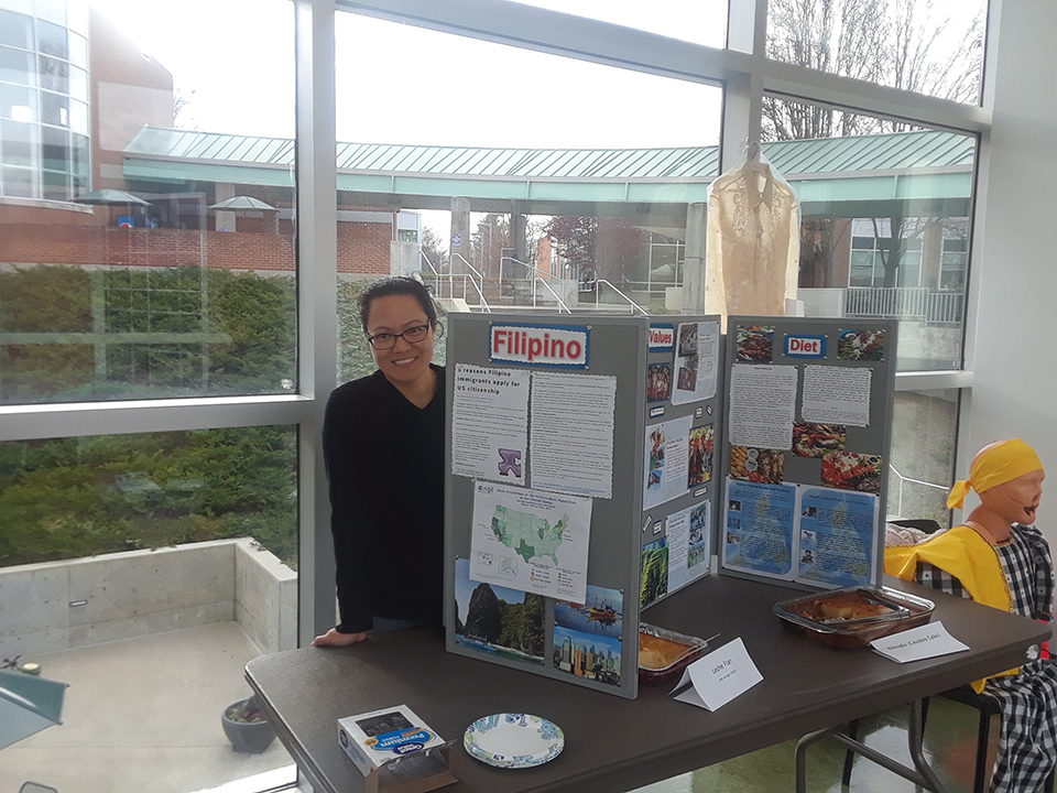 Filipino culture is represented at a table at the Nursing Cultural Fair. A student is seen here with information about the Filipino culture.