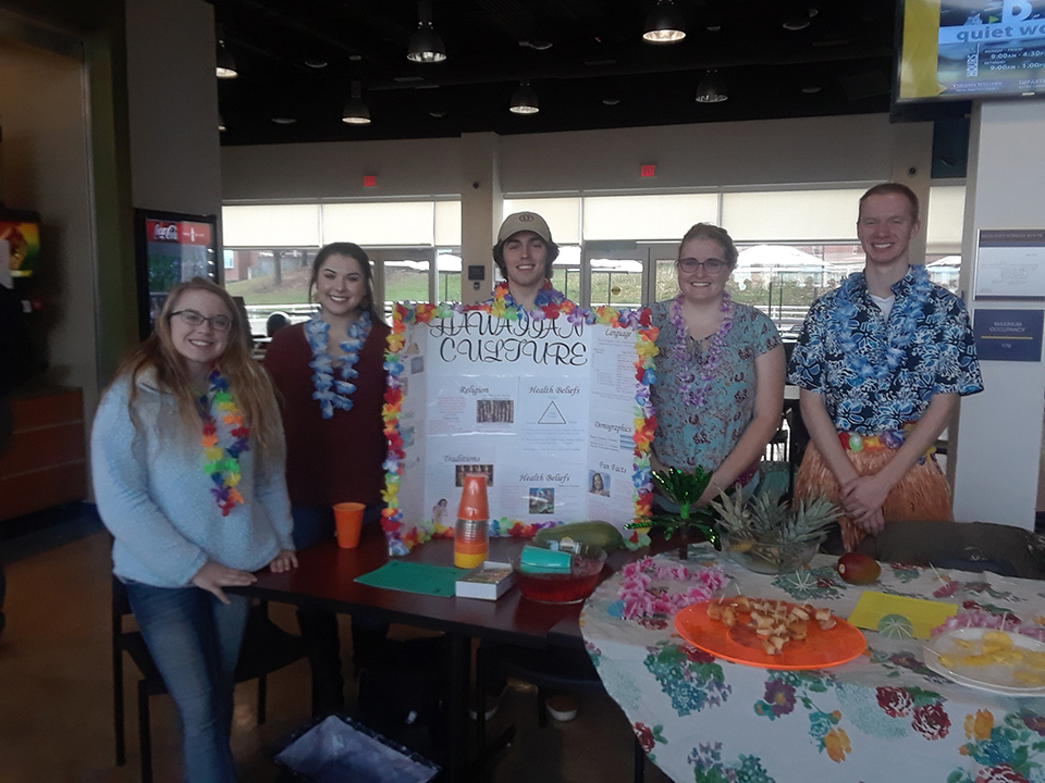 Hawaiian culture is represented at a table at the Nursing Cultural Fair. Students are seen here with information about the Hawaiian culture.