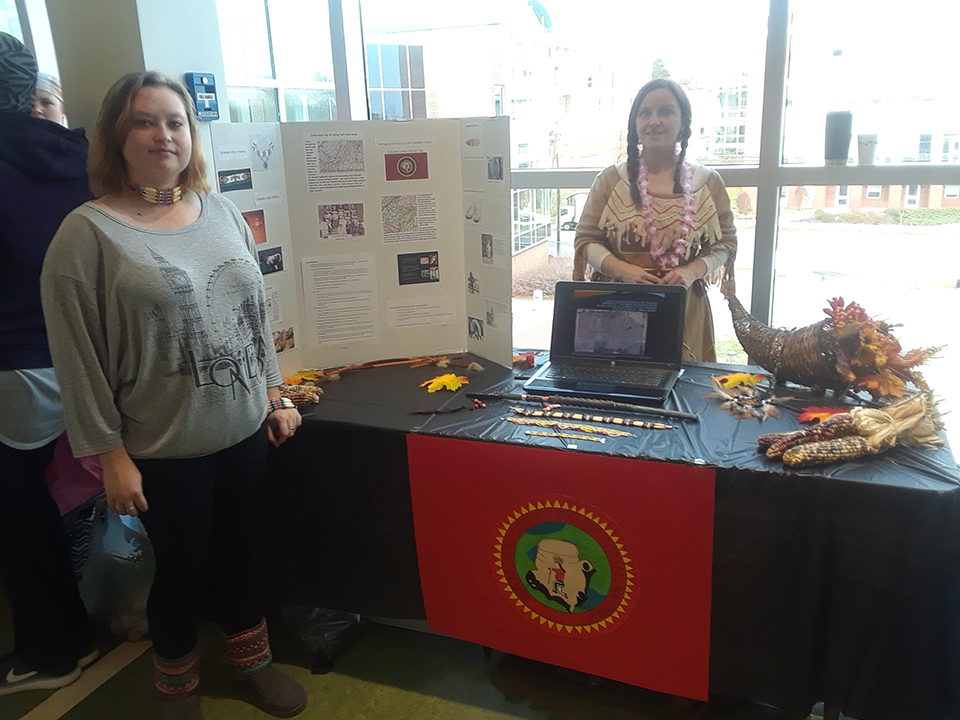 Native American culture is represented at a table at the Nursing Cultural Fair. Students are seen here in traditional dress with artifacts and information about the Native American culture.