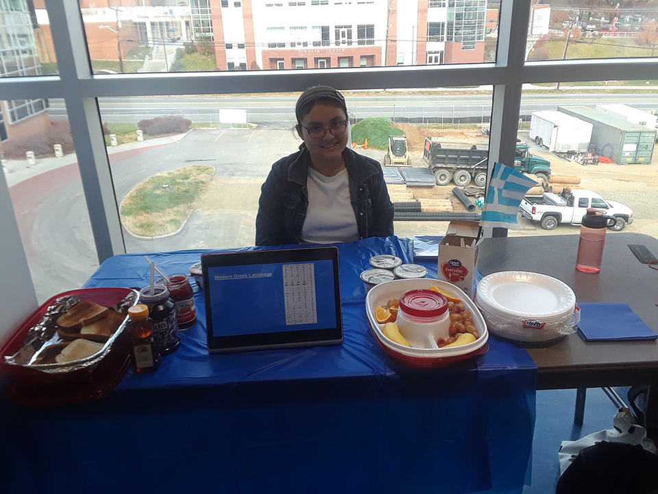 Greek culture is represented at a table at the Nursing Cultural Fair. A student is seen here with information about the Greek culture.