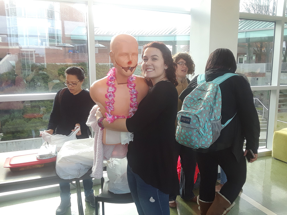 A student holding a mannequin at the Nursing Cultural Fair.