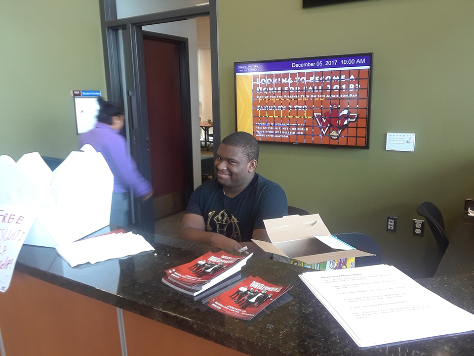 A student smiling at the Student Activities Desk located in the Student Life Building.