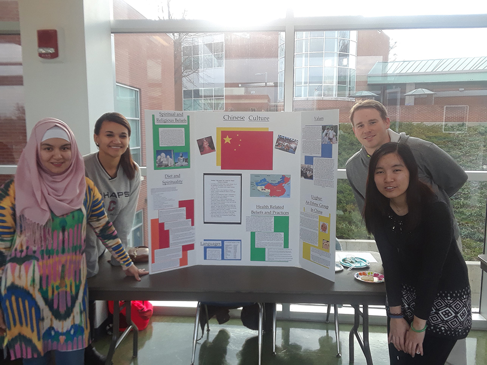 Chinese culture is represented at a table at the Nursing Cultural Fair. Students are seen here with information about the Chinese culture.