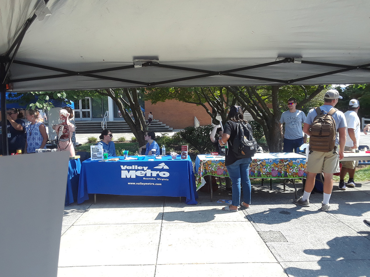 Valley Metro table at the VWCC Welcome Back Event. Students visiting a variety of informational tables.